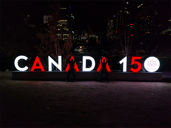 a picture at night of two friends posing as the 'A's' in a Canada 150 sign.