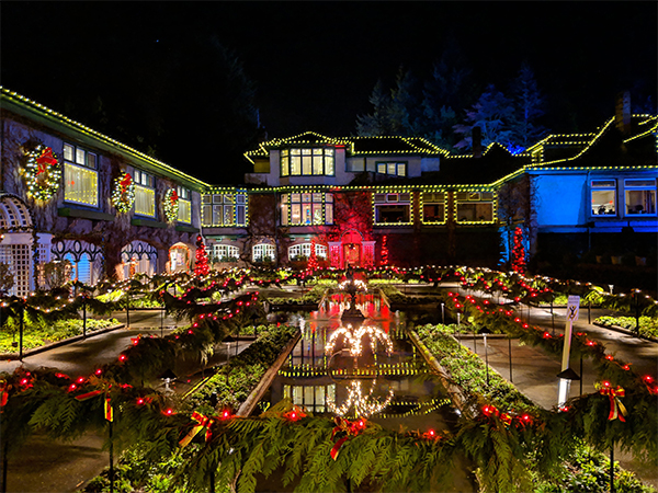 a large house covered in lights during the Butchart Gardens Christmas display.