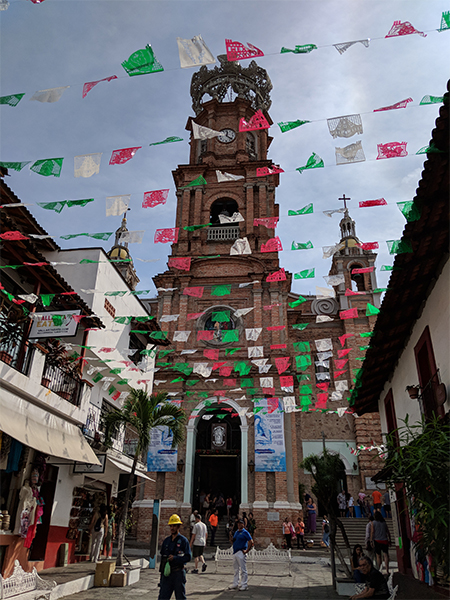 a live look into the streets in Mexico with flags above and a church down the road.